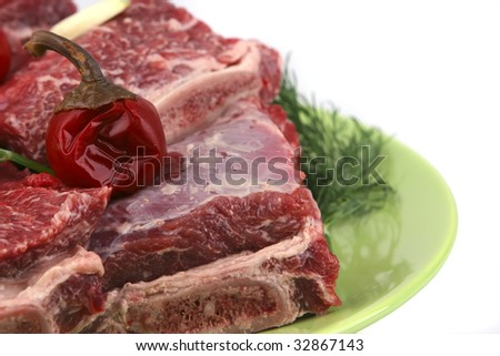 uncooked ribs on green dish over white - stock photo