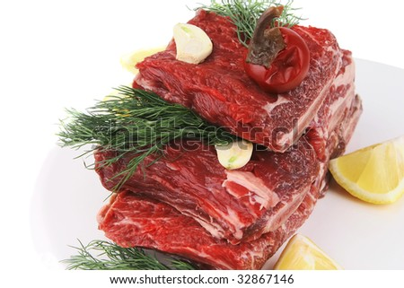 uncooked ribs over white with vegetables and lemon - stock photo
