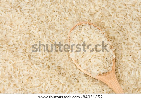 uncooked rice and wood spoon as background - stock photo