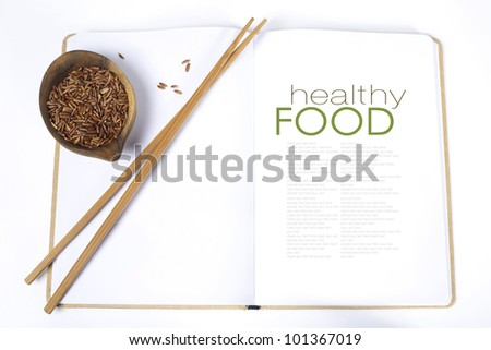 uncooked rice,  chopsticks and opened notebook(with easy removable sample text) - stock photo
