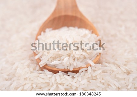 Uncooked rice in a wooden spoon - stock photo