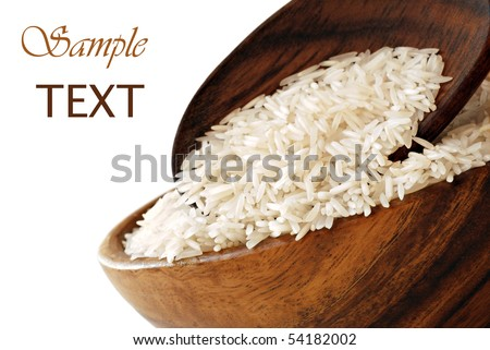 Uncooked rice in wooden bowl with spoon on white background with copy space.  Macro with shallow dof. - stock photo