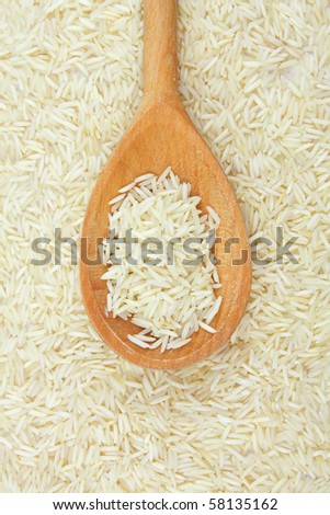 uncooked rice in wooden spoon - stock photo