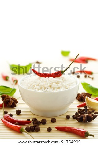 Uncooked rice with spices, herbs and chili peppers - stock photo