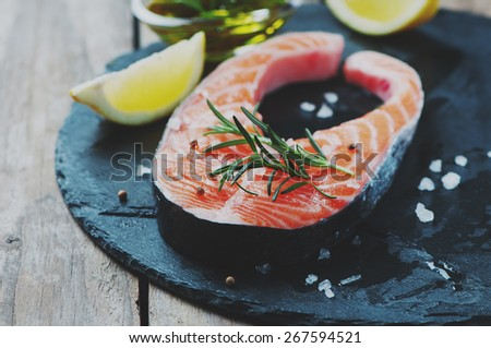Uncooked salmon with rosemary and salt, selective focus and toned images - stock photo