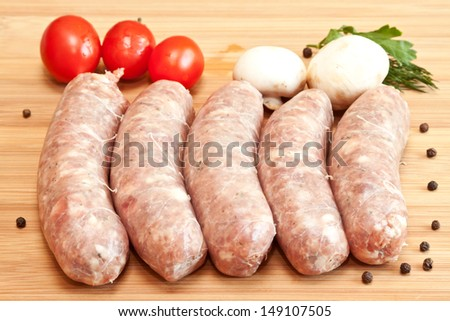 Uncooked sausage with vegetables on the chopping board - stock photo