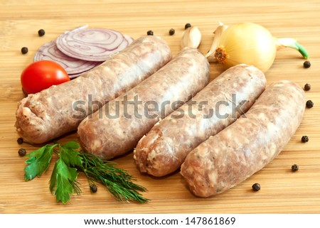 Uncooked sausages with vegetables on the chopping board  - stock photo