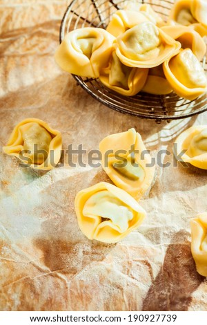 Uncooked savory Italian tortellini ring-shaped pasta for traditional Mediterranean cuisine on crumpled paper on a kitchen counter, high angle view with copyspace - stock photo