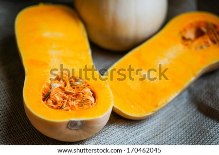 Uncooked sliced butternut squash on wooden background - stock photo