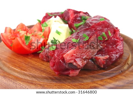 uncooked small beef chunks on wooden plate - stock photo