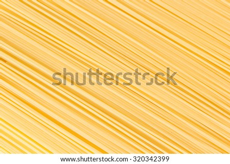 Uncooked spaghetti lie on a diagonal direction - stock photo