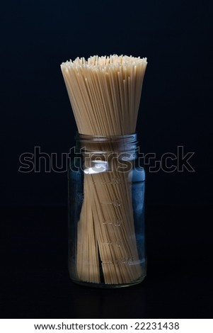 Uncooked spaghetti noodles in jar on black background.