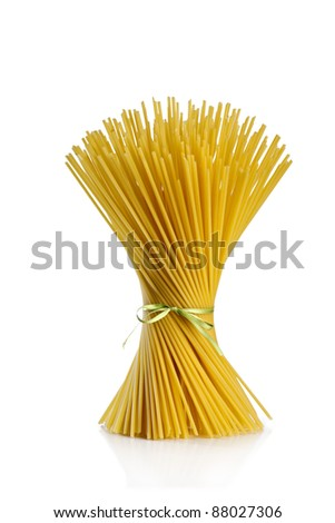 uncooked spaghetti tied with green ribbon on white background - stock photo