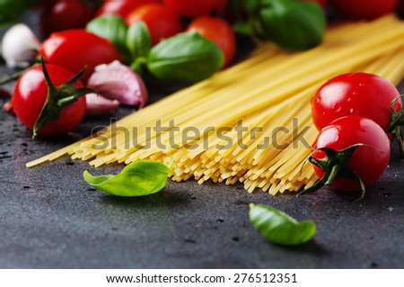 Uncooked spaghetti with tomato and basil, selective focus
