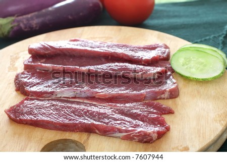 Uncooked thawed out beef slices on a chopping board - stock photo