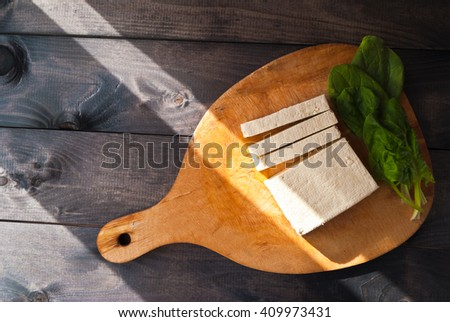 Uncooked tofu slices and green leaves of fresh spinach on cutting board in sunlight. Top view - stock photo