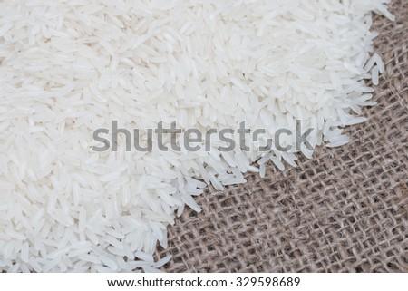 Uncooked white rice (Jasmine Rice)on brown sack. - stock photo