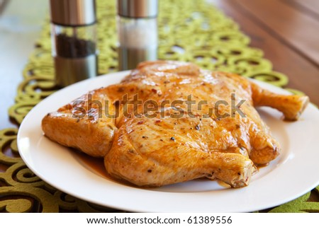 Uncooked whole marinated chicken on a white plate - stock photo