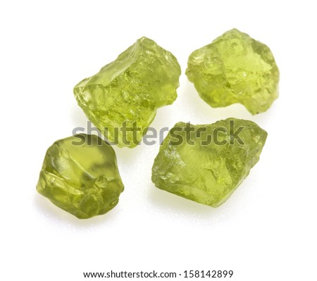 Uncut natural green peridot gems isolated on white background. - stock photo