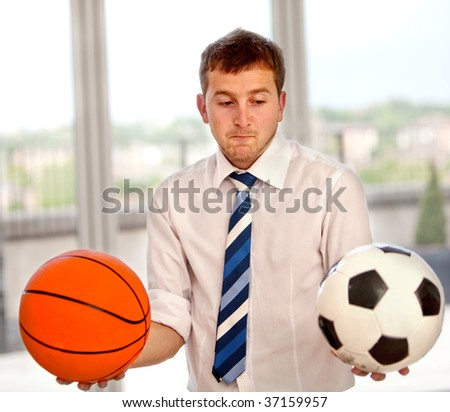 Undecided business man between basketball or football - stock photo