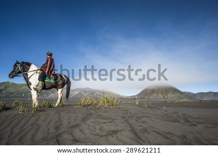 Undefined horse rider transferring tourists around volcano. Mt. Bromo is an active volcano and part of the Tengger massif, in East Java - stock photo