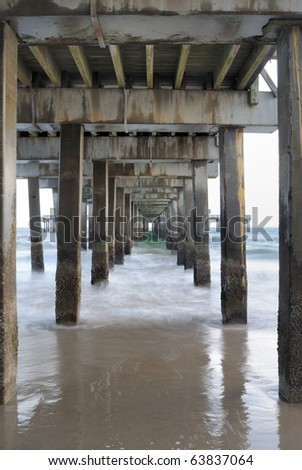 Under a pier on the beach at Coney Island in New York City. - stock photo