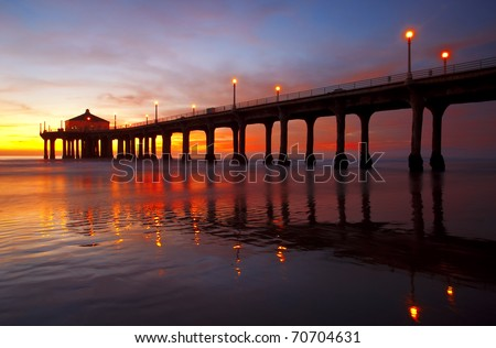 Under a spectacular sunset, Manhattan Beach Pier reflected in the Pacific Ocean - Los Angeles, California. - stock photo