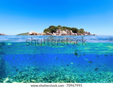 Under and above water photo of small island in Seychelles - stock photo