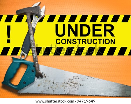 Under construction board with construction right tools - stock photo
