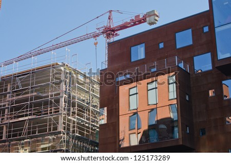 under construction building near to a new building - stock photo