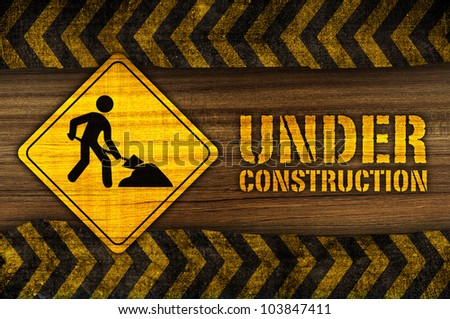 under construction sign on wood texture - stock photo