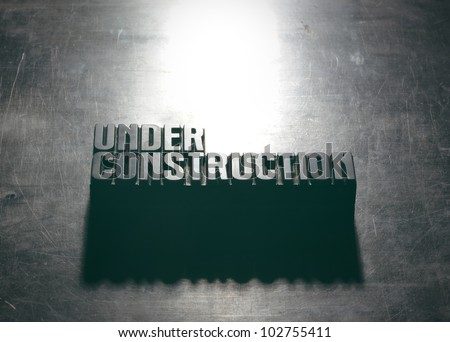 Under Construction sign with a metallic background texture - stock photo