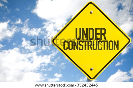 Under Construction sign with sky background - stock photo