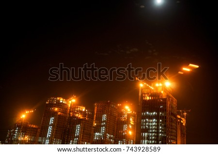 Under construction sky scraper with cranes, working lights shot against a moonlit cloudy sky. One of the number of projects that have started in Gurgaon, Noida, Delhi, Hyderabad, Bangalore real estate