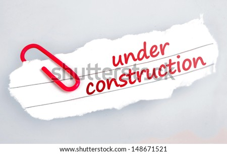 Under construction word on grey background  - stock photo