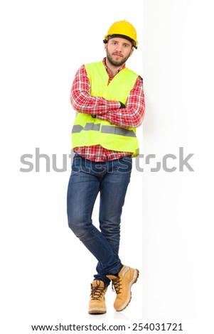 Under construction. Worker in yellow helmet and reflective lime waistcoat lean on a wall and holding arms crossed. Full length studio shot isolated on white.