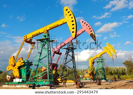 Under sunny golden yellow and pink Oil pump oil rig energy industrial machine for petroleum crude of countryside,dirt road - stock photo