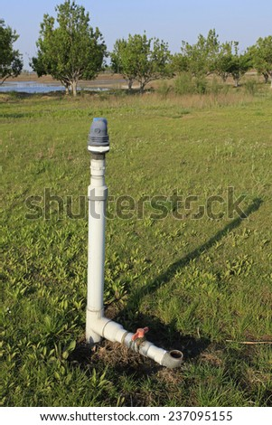 Under the blue sky white clouds lawn sprinkler water-saving irrigation - stock photo