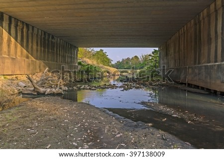 Under the bridge : Peaceful and Tranquil nature - river flowing through natural cascades and wet rock and sand with sunlight shining. - stock photo
