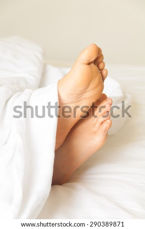 Under the covers with feet showing in a bed - stock photo