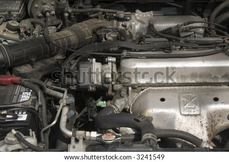 Under the hood of a car: partial view of engine and battery, hoses, radiator, cables - stock photo