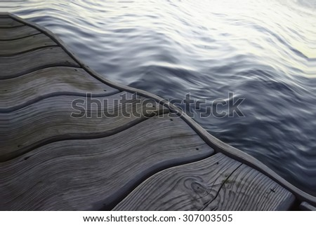 Under the influence: Wavy wooden dock by water reflecting light from the rising sun, for themes of fluidity or altered states of mind - stock photo