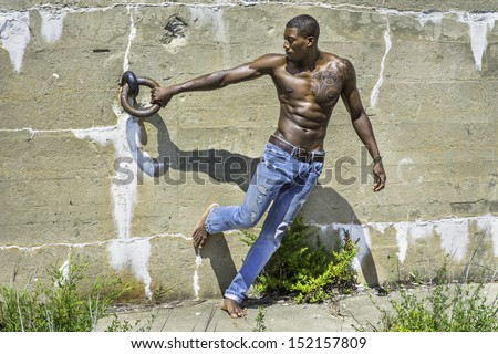 Under the sunshine, a masculine black guy, wearing blue jeans, barefoot and half naked, is standing by a wall and holding a metal ring. / Portrait of  Young Black Fitness Guy - stock photo