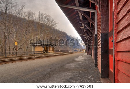 Under the Train Station Eaves - view down tracks towards tunnel - stock photo