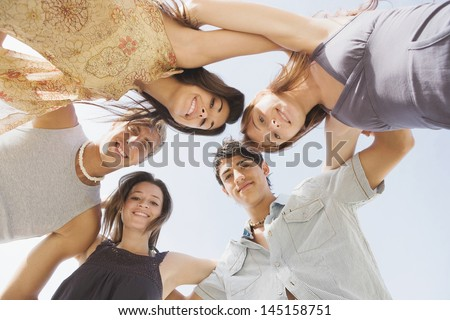 Under view of a group of five teenagers friends looking down at the camera with their arms around each others shoulders against a sunny sky while on vacation during the summer break. - stock photo