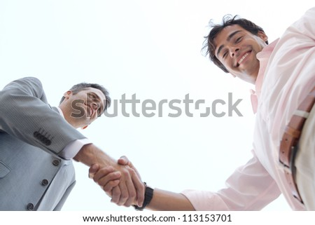 Under view of two businessmen shaking hands against the sky, smiling. - stock photo