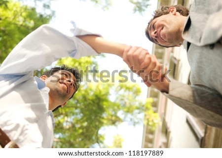 Under view perspective of two young attractive businessmen shaking hands against a blue sky with trees in the city. - stock photo