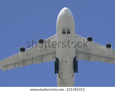 Undercarriage of a plane showing the landing gear descending - stock photo