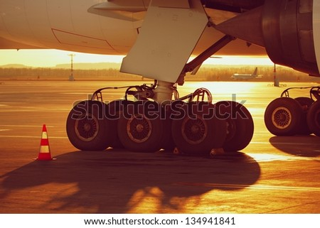 Undercarriage of the huge airplane at the sunset - stock photo