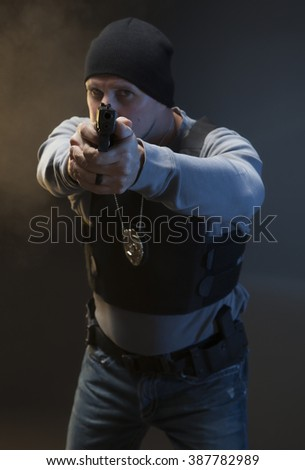 Undercover Law Enforcement Special Agent with weapon. Police officer dealing with an active shooter with smoke in background. - stock photo